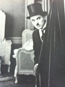 Charlie Chaplin hiding behind a black velvet curtain in Hollywood Babylon